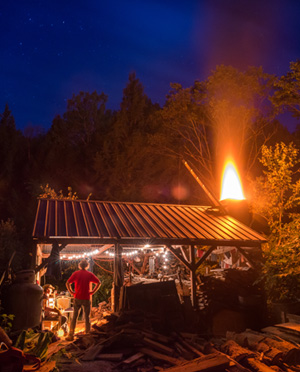 Ceramics Professor Jon Keenan manages a wood fired kiln against a night sky