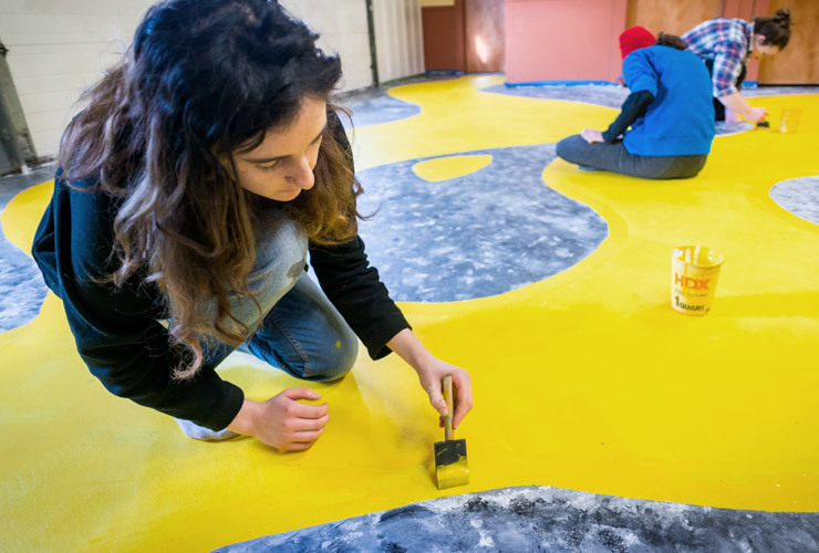 Colby-Sawyer art students paint an abstract design onto commercial floor