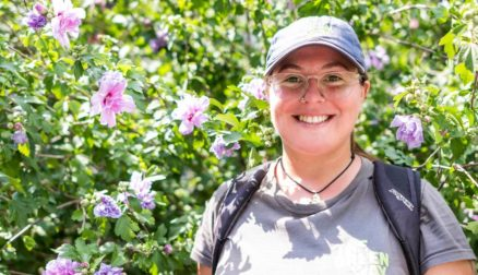 Colby-Sawyer student Nicole Sememaro '18 smiles in front of a flowering shrub.