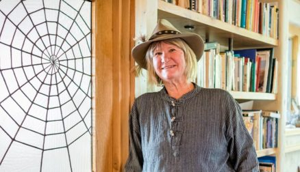 Joan Montagne stands in front of a wooden door with a large glass panel etched with a spider web.