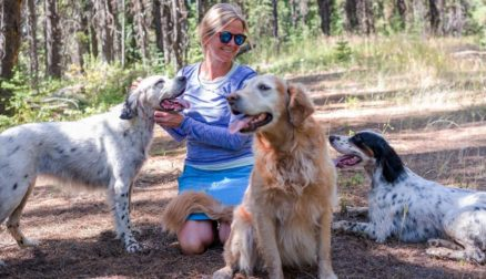 Joanne sitting on a trail with her three dogs.