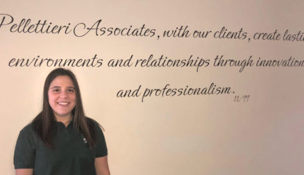 "Lauren Blanchard '18 stands in front of one of PAI's mission statements that reads ""Pellettieri Associates, with our clients, create lasting environments and relationships through innovation and professionalism."""