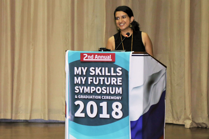 Kavyaa Rizal standing at a podium at a conference.