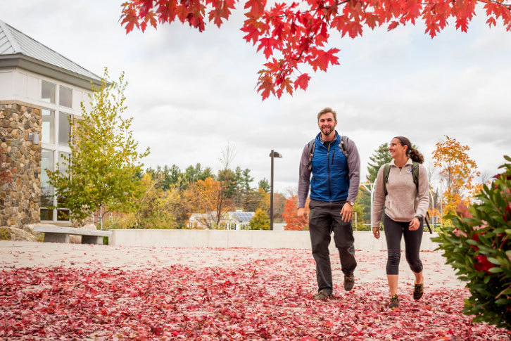 Two students walking down a sidewalk covered with red leaves.