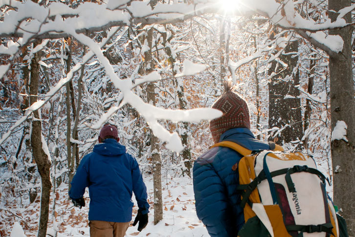 Two Colby-Sawyer students hiking on snow covered trail in the forest.