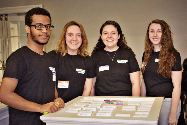 Residential Assistant Nate Feleke stands with three other student leaders at leadership retreat.