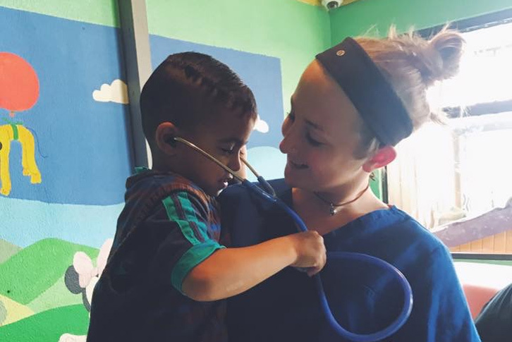Brittany Ireland holds a little boy as he uses a stethoscope to listen to her heart.