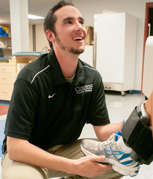 Kevin Flaherty '14 adjusts a leg brace on fellow Colby-Sawyer student