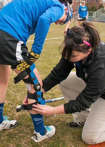 Athletic Training Student helping a player on the field