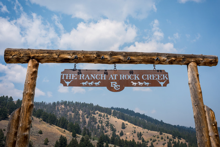 A copper sign hanging beneath a wooden arch that reads: The Ranch at Rock Creek.