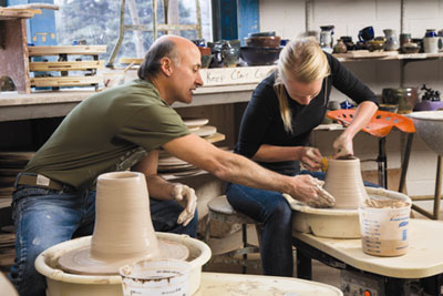 Dave Ernster assists senior Kate Rial as she shapes a vessel on the throwing wheel. 'The thing that draws me to the art of ceramics is the feeling of clay between my hands — how one can manipulate it into anything they wish, and then recycle it to create something completely new, excites me and allows me to make mistakes and challenge myself as an artist,' says Rial