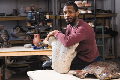 Michael Bacote '13, a Studio Art major with a concentration in Ceramics, shows some of his figurative Raku work in the Ceramics Studio.