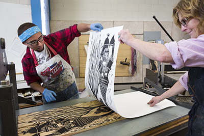 Will Shearer and Professor Mead lift a print from his woodcut block.